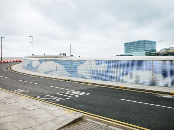 Blue sky and clouds stencilled on concrete wall leading to the 2012 Olympic park