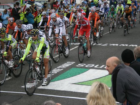 Road cyclists racing past the 7 Stanes logo applied to the road for the Tour of Britain event in Dumfries & Galloway