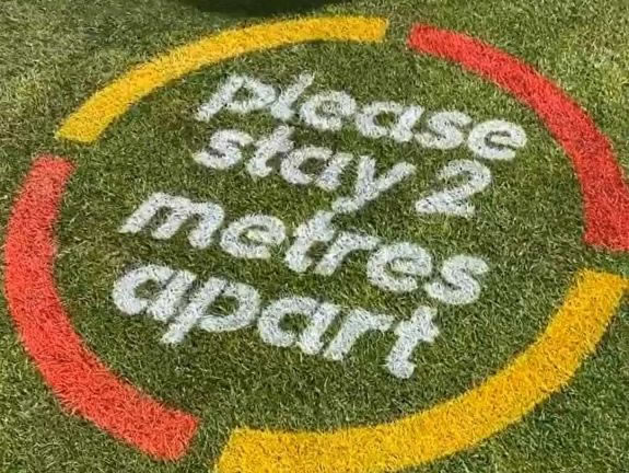 Social Distancing message applied to grass with chalk spray